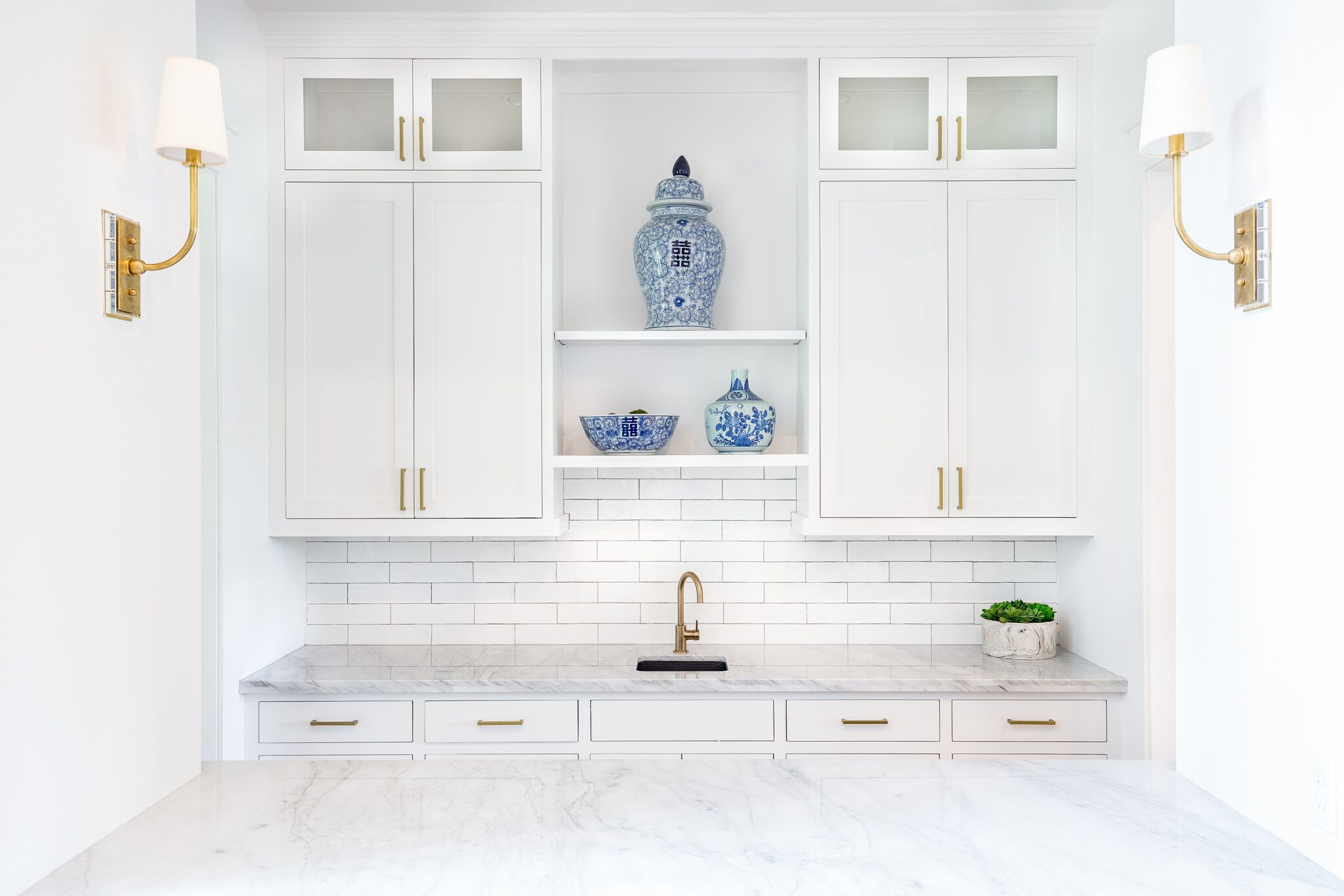 Come see this modern farmhouse featuring a built in wet bar off of the living room with gold cabinet hardware and a long white subway tile backsplash.