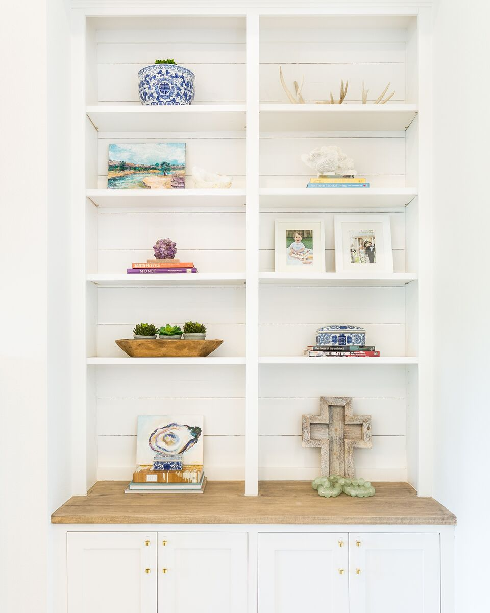 Come see this modern farmhouse featuring these built in shelves in the living room with shiplap, reclaimed wood, and brass and lucite pulls.