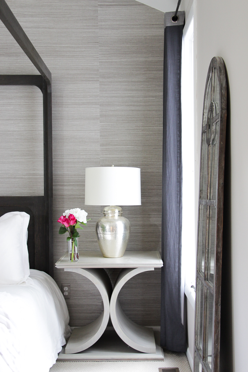 Click to see this drastic master bedroom makeover featuring all white bedding, grasscloth wallpaper, custom open nightstands, and a wood canopy bed!