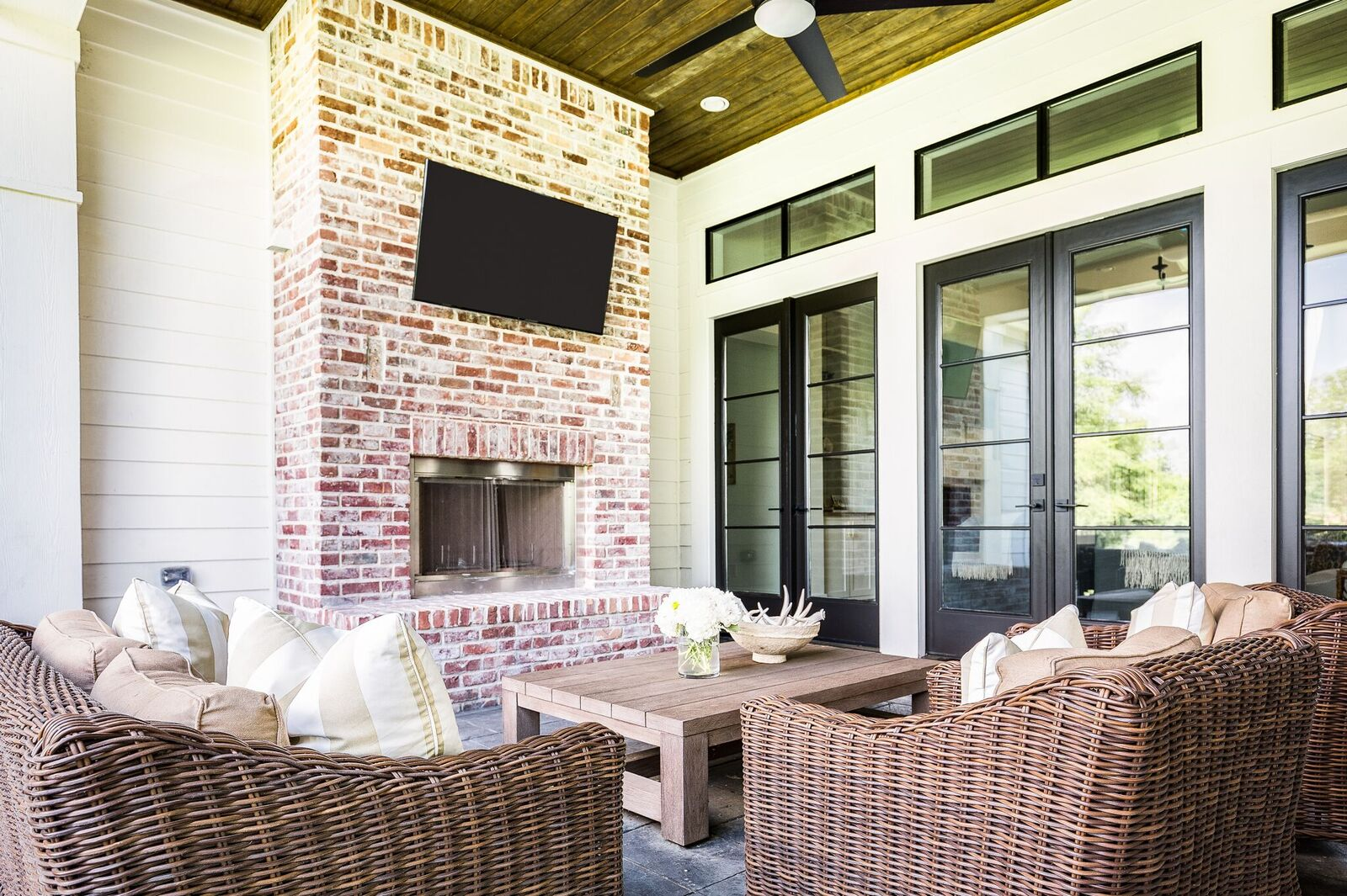 Come see this waterfront modern farmhouse featuring a covered patio over an outdoor living room.