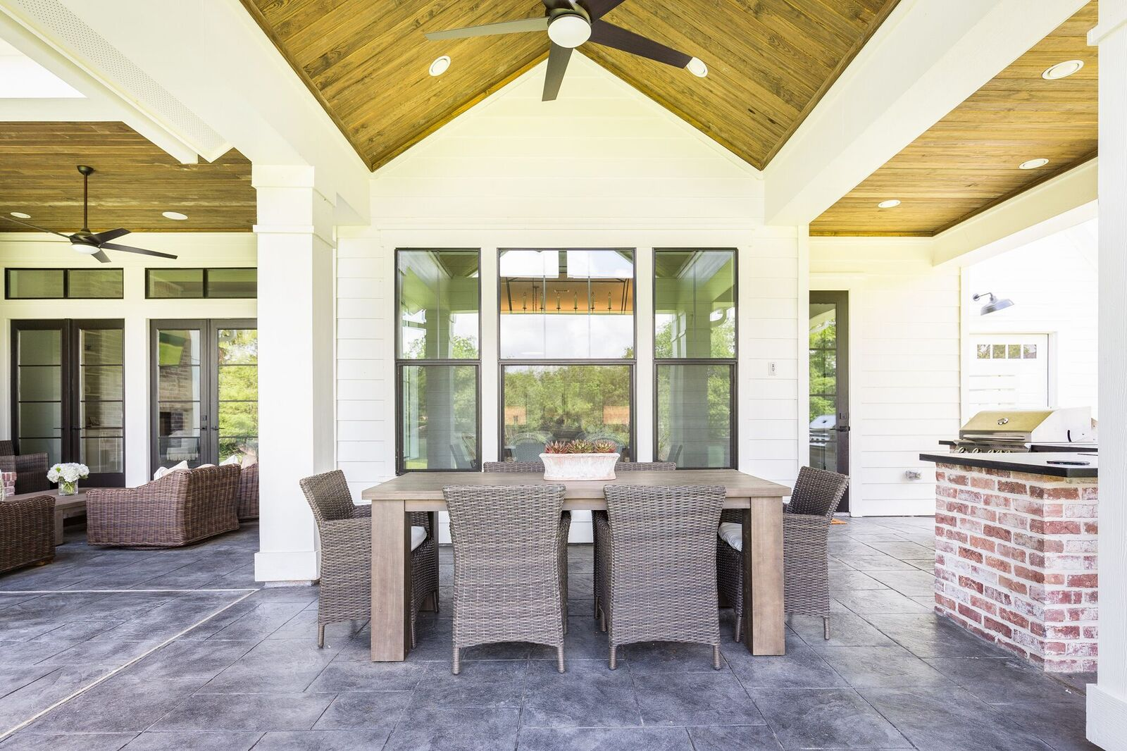 Come see this waterfront modern farmhouse featuring a covered patio over an outdoor dining room.