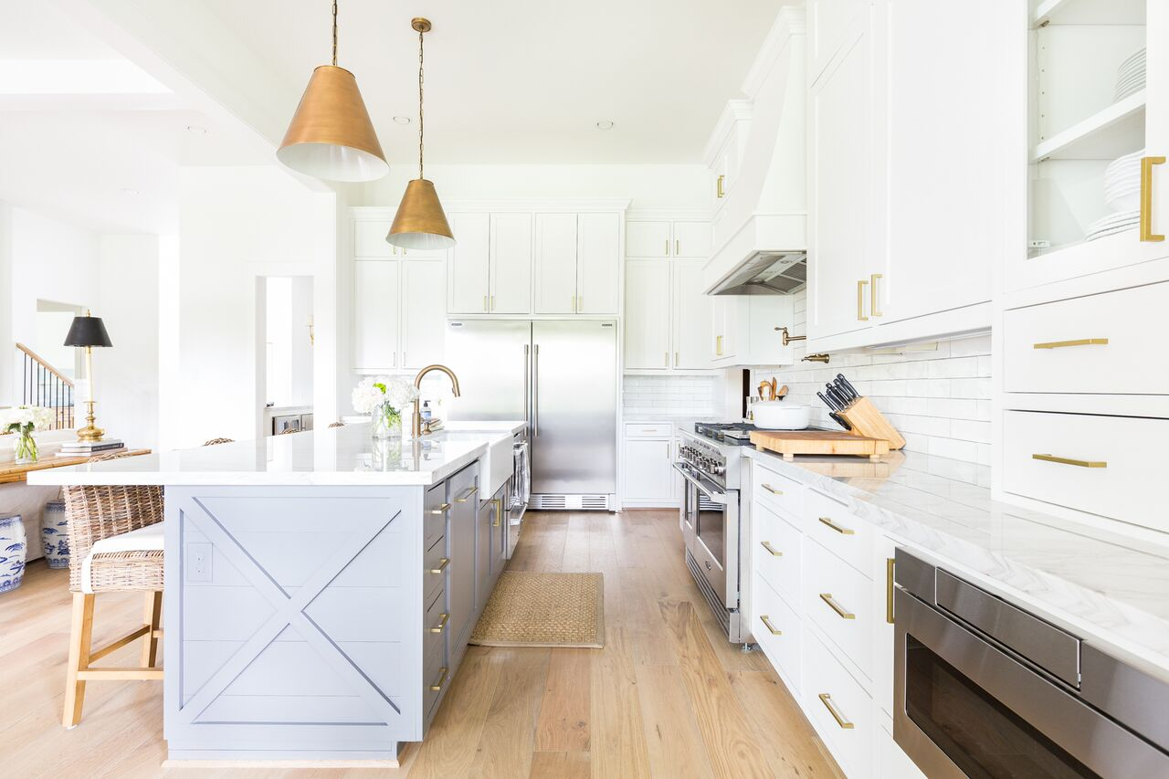 Come see this modern farmhouse featuring an open concept kitchen and living room with gold pendant lighting, wicker bar stools, and a two tone kitchen island.