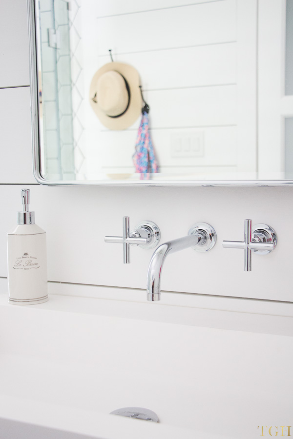Modern farmhouse bathroom makeover featuring a wall mounted faucet, trough sink, and shiplap