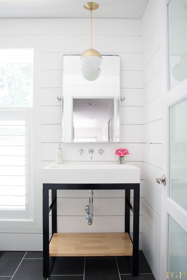 White modern bathroom makeover with a wall mounted faucet, steel vanity, trough sink and shiplap