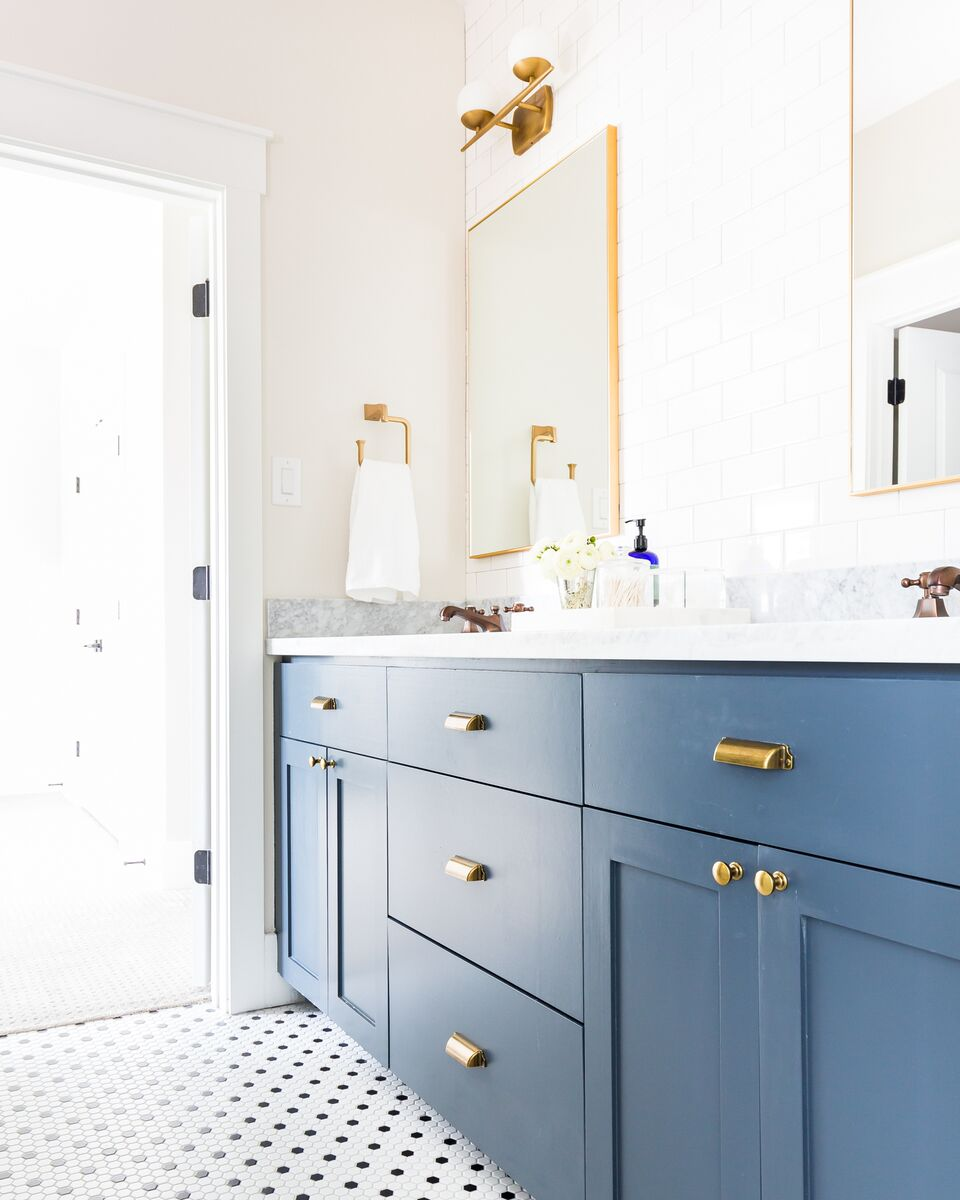 Come see this luxury home featuring a guest bathroom with brass mirrors, white subway tile, and a navy vanity.