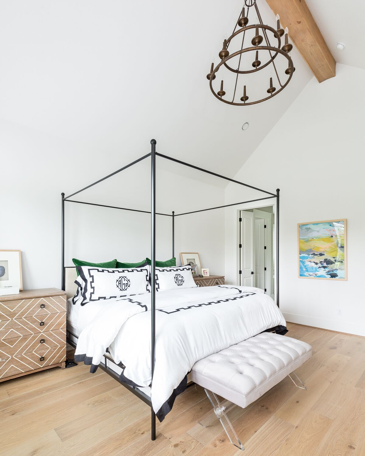 Come see this modern farmhouse featuring a master bedroom with an iron canopy bed and white oak engineered hardwood floors.