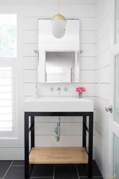 White modern bathroom makeover with a custom steel bathroom vanity, brass pendant, and shiplap