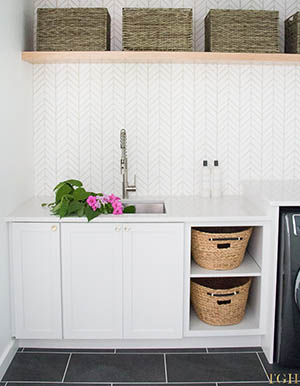 Modern laundry room remodel with open shelving, built in laundry hampers, and a folding counter.