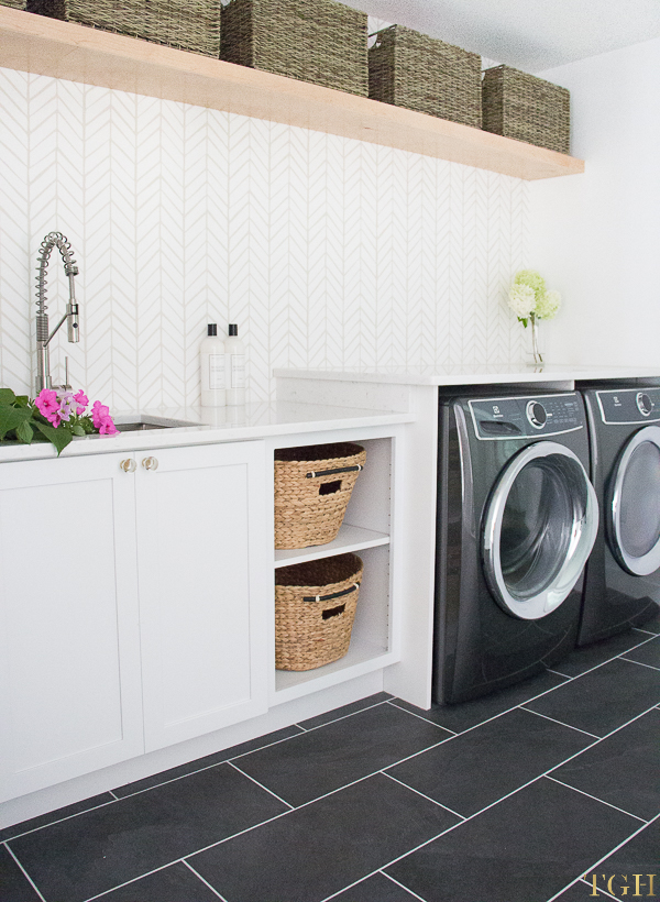 Come see this modern laundry room remodel featuring open shelving and a white quartz countertop over the washer and dryer.