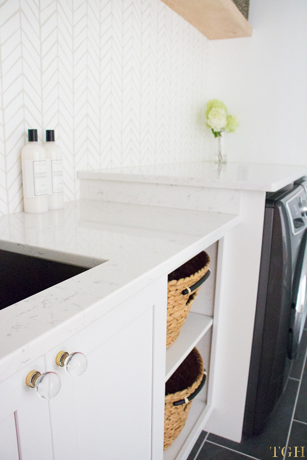 Come see this modern laundry room remodel with glass cabinet knobs and white quartz waterfall countertop.