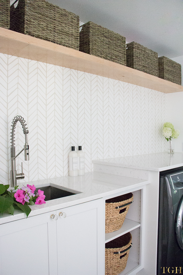 Come see this modern laundry room renovation with open shelving and baskets for storage.
