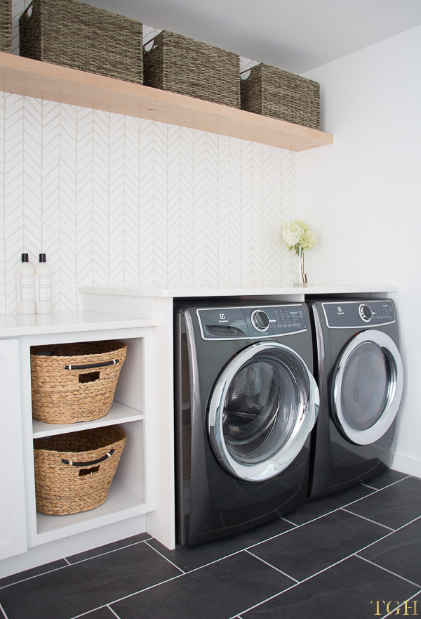Come see this modern laundry room remodel with a white quartz counter over the washer and dryer and built in laundry cabinets.