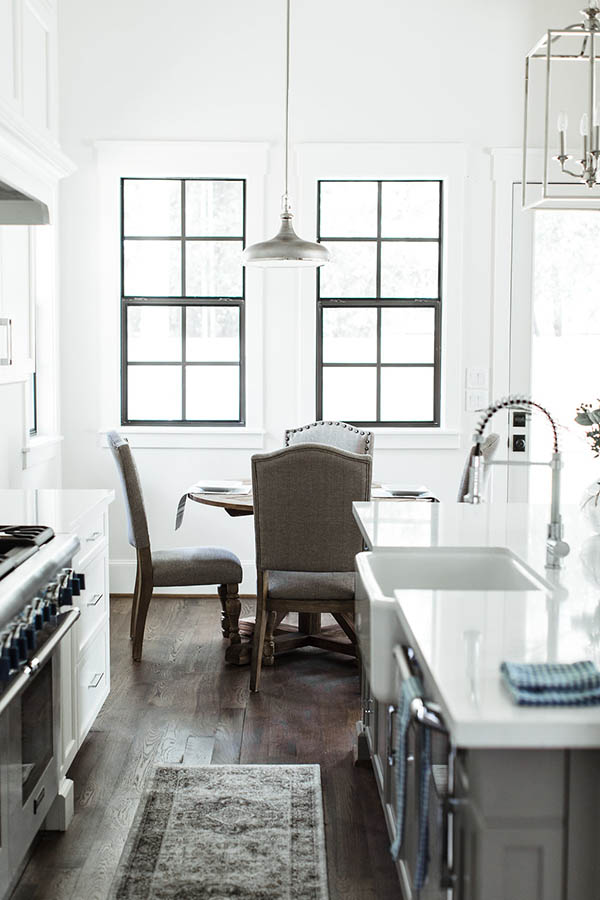 Black trim windows kitchen. Breakfast nook table round. Modern farmhouse kitchen black and white.