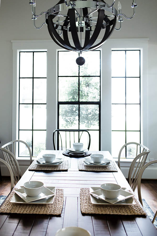 Black trim windows farmhouse. Modern farmhouse dining table and chairs. Dining room chandelier transitional.