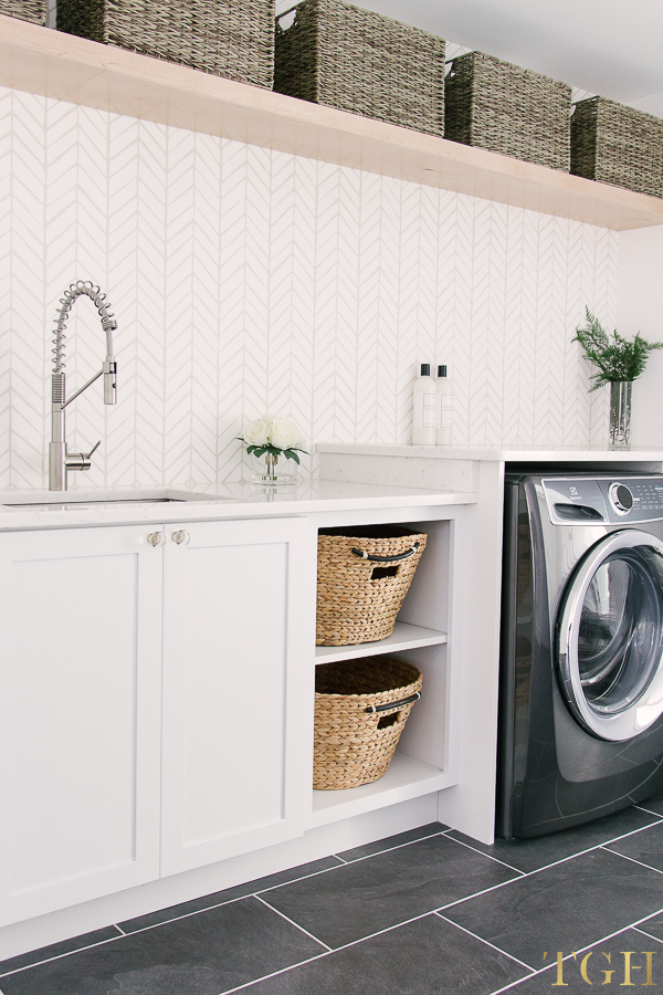 Laundry room with open shelving, built in laundry baskets, wallpaper, and a folding counter.