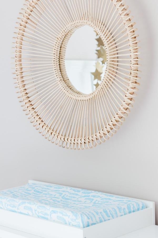 Rattan mirror over white changing table
