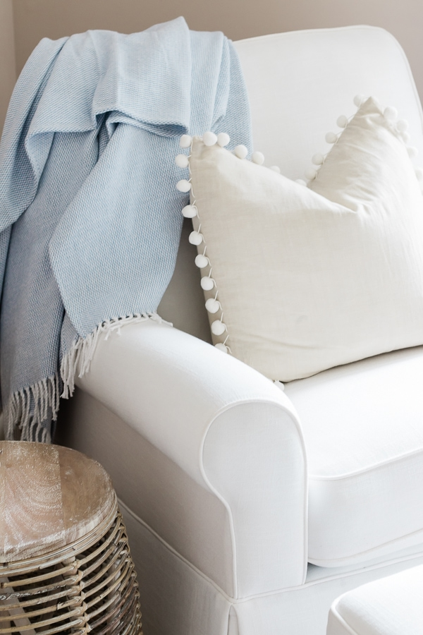 White glider in baby boy nursery with rattan side table and a pom pom pillow